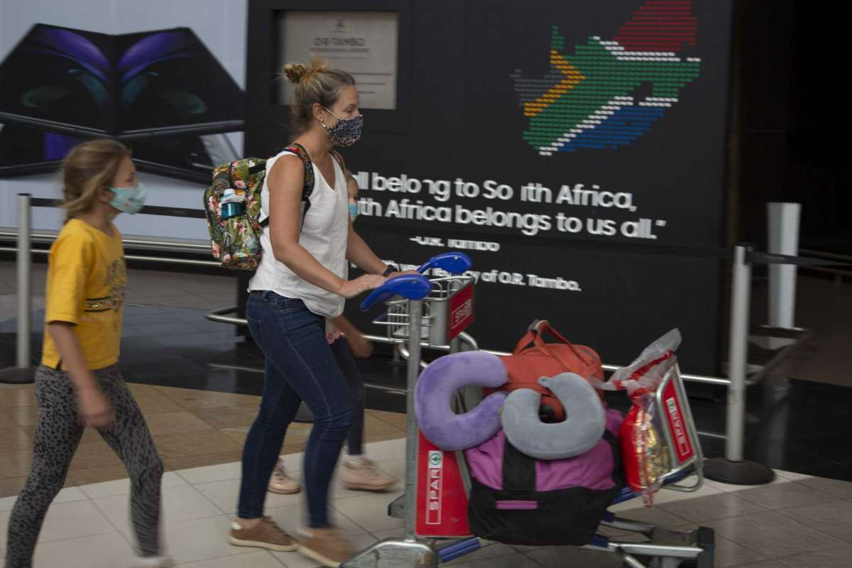 Woman with 2 daughters pushing luggage trolley at South Africa 's OR Tambo Airport Arrivals